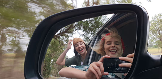 Two people taking their picture in a car side mirror