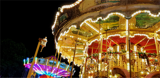 A colourful and brightly lit carrousel at night